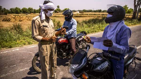 A police officers wearing a protective mask questions a motorcyclist at a checkpoint in the Gautam Buddh Nagar district of Uttar Pradesh (Bloomberg)