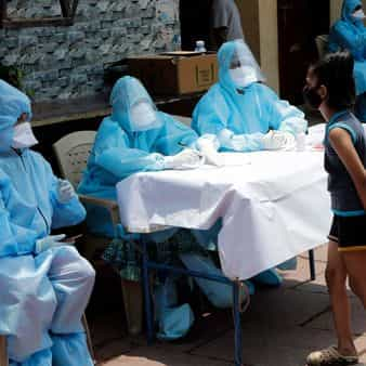 Doctors speak with a girl during a free medical camp in Dharavi, Mumbai, during the covid-19 lockdown. (Photo:AP)