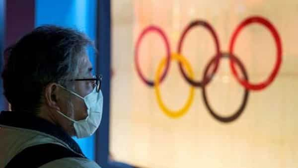FILE PHOTO: A man wearing a protective face mask, following an outbreak of the coronavirus, stands in front of The Tokyo Olympic flag 1964 at The Japan Olympics museum in Tokyo, Japan, February 26, 2020. REUTERS/Athit Perawongmetha (REUTERS)