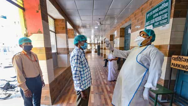 An employee conducts thermal scanning of visitors arriving at a civil hospital after OPD started functioning during the nationwide lockdown, (PTI)