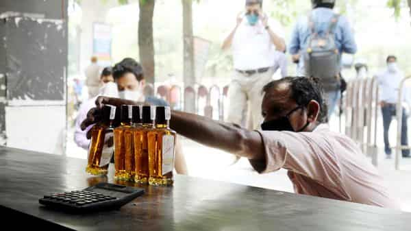 A man buying alcohol from wine shop after authorities allowed sale of liquor with certain restrictions, during the ongoing COVID-19 nationwide lockdown, in