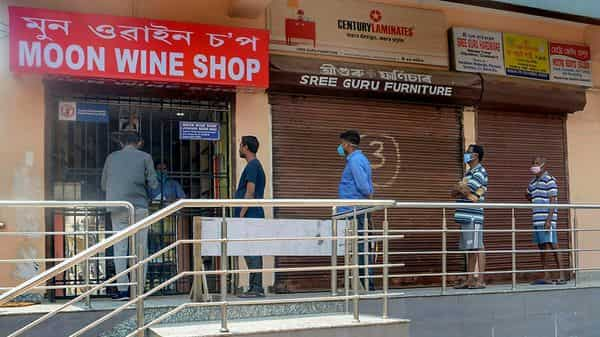 People maintain social distance as they stand in a queue outside a wine shop, during the nationwide lockdown to curb the spread of coronavirus, in Guwahati. (PTI)