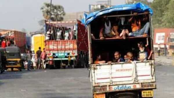A truck carrying migrant workers leaves for Uttar Pradesh, on the outskirts of Mumbai, Thursday. (AP)