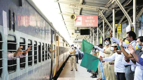 Passengers wave as officials flag off a train carrying migrants to Uttar Pradesh at Kolhapur railway station on Friday. (Photo: PTI)