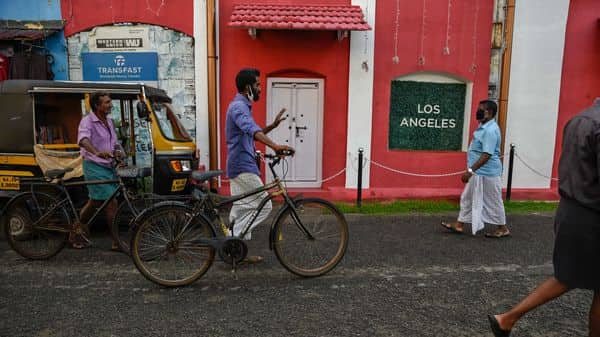 People, some of them wearing masks walk past a cafe frequented by tourists currently remaining closed due to the COVID-19 pandemic in Kochi, Kerala (AP)