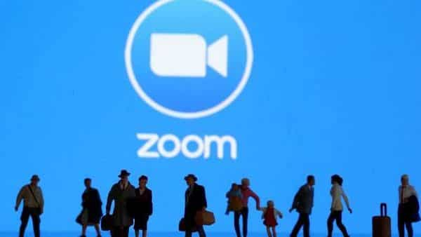 FILE PHOTO: Small toy figures are seen in front of diplayed Zoom logo in this illustration (REUTERS)
