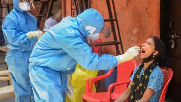 Mumbai: A healthcare worker collects swab sample of a Shahid Bhagat Singh Nagar resident for COVID- 19 test, during the ongoing nationwide lockdown, at Dharavi slum area in Mumbai, Wednesday, May 20, 2020. (PTI)