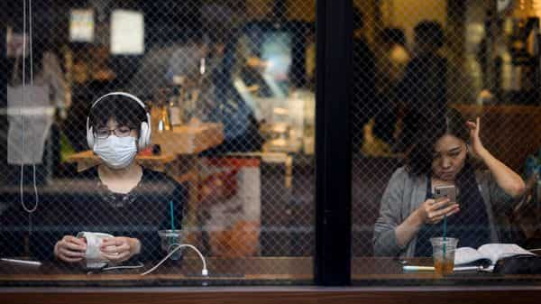 People sit in a cafe in Sugamo district of Tokyo