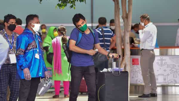 Passengers leave for a quarantine centre as they check-out from the Kempegowda International Airport, in Bengaluru, Monday. (PTI)