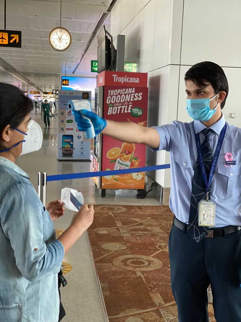 Airline officials checking temperature before a passenger boards the flight. Airports will now also maintain staff near washrooms, X-ray machines, conveyor belts to implement social distancing among passengers.