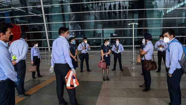 Indigo airlines staff get a briefing at the Indira Gandhi International airport in Delhi after the government eased a nationwide lockdown imposed as a preventive measure against the COVID-19 coronavirus. (AFP)