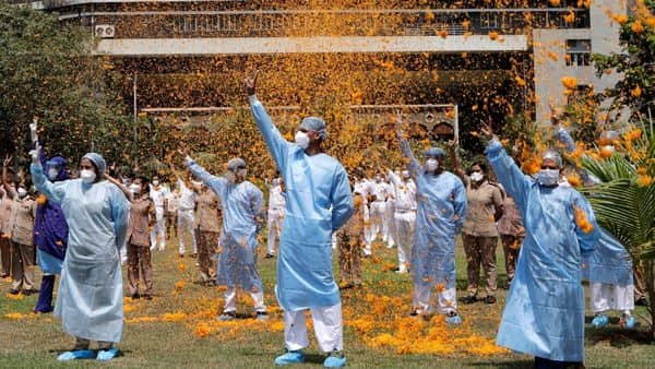 An Indian Air Force helicopter showers flower petals on the staff of INS Asvini hospital in Mumbai (AP)