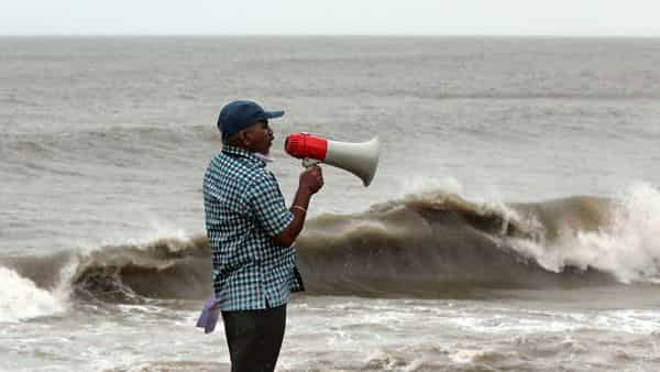 A BMC official makes an announcement at a sea facing promenade asking people to stay away from the sea before the arrival of cyclone 'Nisarga' in Mumbai on Wednesday. (ANI Photo)
