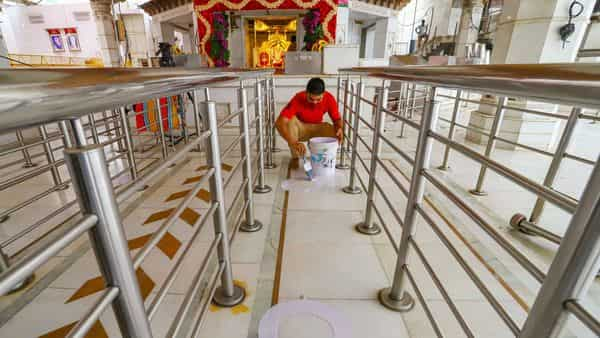 New Delhi: A worker paints circles on the floor of Jhandewala Devi Mandir to help maintain the social distancing norms, ahead of its reopening, in New Delhi (PTI)