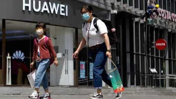 Residents wearing face masks to protect against the coronavirus walk past a Huawei retail store in Beijing. (AP)