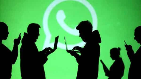 FILE PHOTO: Silhouettes of laptop and mobile device users are seen next to a screen projection of Whatsapp logo in this picture illustration taken March 28, 2018. REUTERS/Dado Ruvic/Illustration