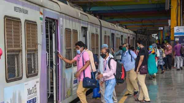 People board a local train after services resumed for people in essential services, during the nationwide lockdown to curb the spread of coronavirus, in Mumbai. (PTI)