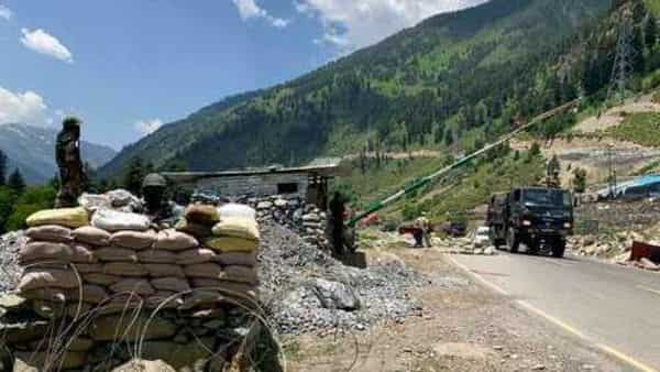 Indian soldiers keep guard as Indian army convoy moves on the Srinagar- Ladakh highway at Gagangeer, north-east of Srinagar (Photo: AP)