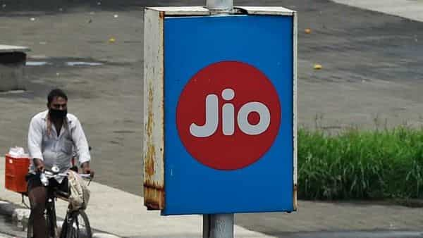 A cyclist passes by an advertising board of Reliance Jio, a digital platform owned by Indian businessman Mukesh Ambani's Reliance Industries,