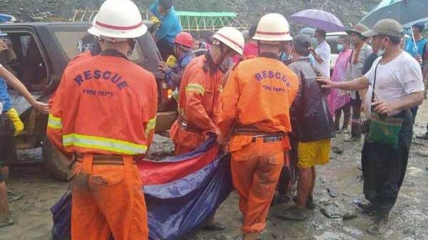 Rescue workers carry a dead body following a landslide at a mining site in Phakant in Kachin State City in Myanmar  (Reuters)