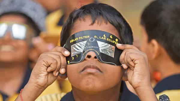 A boy uses solar filter glasses to view a rare 'ring of fire' solar eclipse at a school in Mumbai on 26 December 2019. getty images