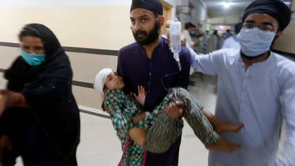 People carry a girl, who was injured in bus and train accident, after receiving initial treatment at a hospital in Sheikhupura near Lahore (AP)