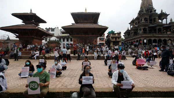 Nepalese youths holding placards as they protest demanding better and effective response from the government to fight the coronavirus  (REUTERS)