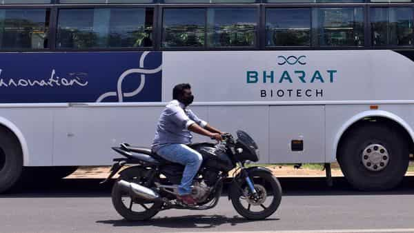 A man rides his motorbike past a parked bus of biotechnology company Bharat Biotech outside its office in Hyderabad (Reuters)