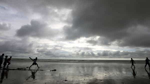 Silhouette of boys play cricket as the dark monsoon clouds hover the sky, at Juhu beach in Mumbai on Friday. (ANI Photo)