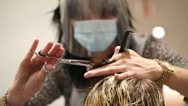 A stylist cuts the hair of a client in Camden, London, after opening at midnight to the first post-lockdown customer as restrictions are eased across England early Saturday. (AP)