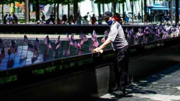 A worker disinfects the area of one of the reflecting pools as people visit the 9/11 Memorial Plaza during its reopening after having been closed for more than three months amid the coronavirus pandemic. (AP)