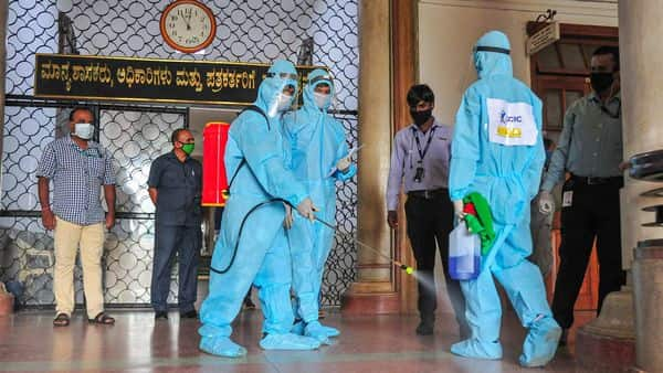 Workers wearing PPE spray disinfectants at Vidhana Soudha corridor, after a police person tested COVID-19 positive, in Bengaluru (PTI)