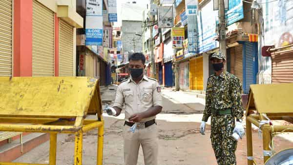 Bengaluru: Police and BBMP personnel seal Sadar Patrappa road as the state government announced strict lockdown due to surge in COVID-19 cases in the area. (PTI)
