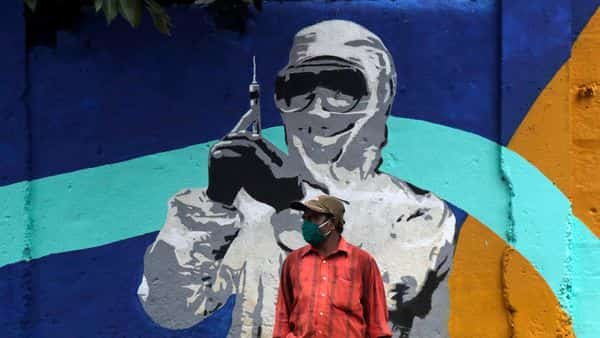 A man stands in front of a graffiti honoring those in the frontlines in the fight against the coronavirus in Mumbai (AP)