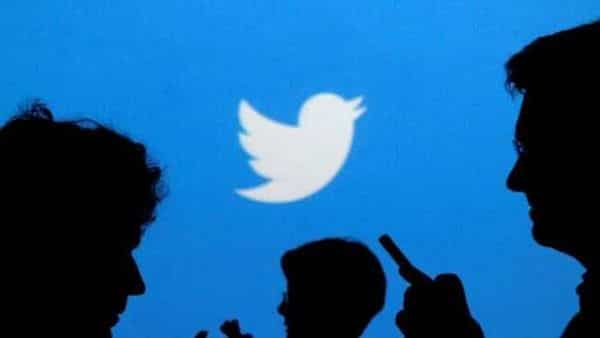 FILE PHOTO -- People holding mobile phones are silhouetted against a backdrop projected with the Twitter logo  (Reuters)