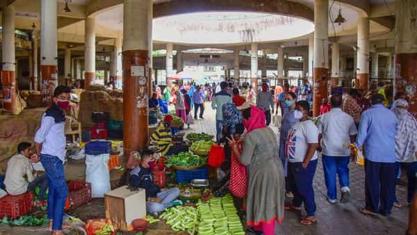 People buy vegetables in a market, after authorities announced a 10-day total lockdown from July 14 in Pune. (PTI)