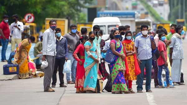People wait for means of transportation as they leave the city after authorities announcedweek-long lockdown due to surge in Covid-19 cases, in Bengaluru, Monday (PTI)