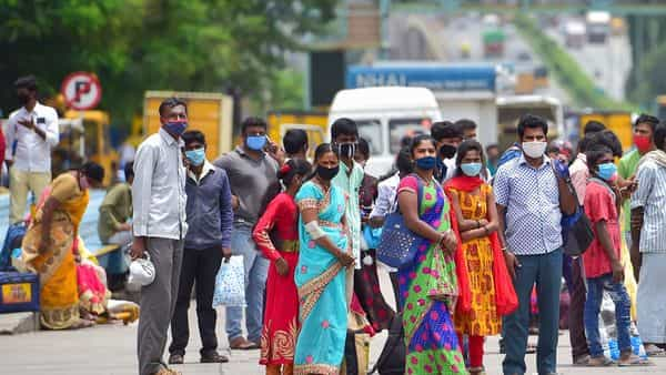 People wait for transport as they leave the city after authorities announced a week-long lockdown due to surge in Covid-19 cases, in Bengaluru. (Photo:PTI)