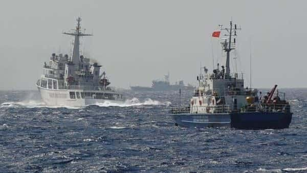 A file photo of a Chinese coast guard vessel (left), followed by a Vietnamese coast guard ship, in South China Sea.