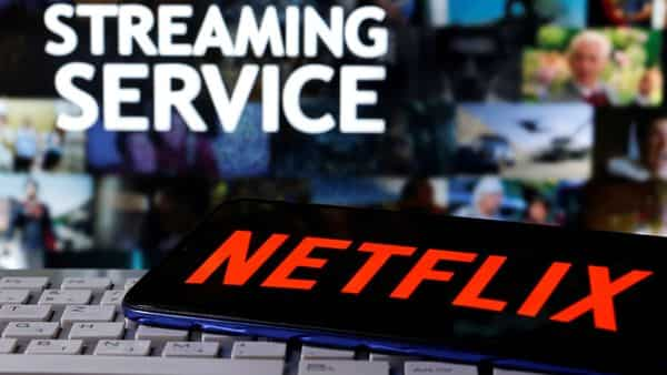 A smartphone with the Netflix logo is seen on a keyboard in front of displayed 'Streaming service' words in this illustration (REUTERS)