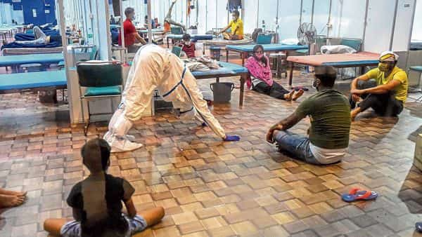 A health worker in a PPE suit demonstrates a yoga asana for patients at a temporary covid-19 ward in New Delhi's Commonwealth Games Village on Thursday. (AFP)