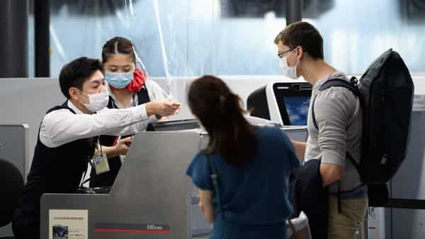 Employees wearing protective masks, left, assist passengers behind a plastic barrier at the Air France-KLM Group check-in desk inside Narita Airport in Narita, Chiba Prefecture, Japan, (Bloomberg)