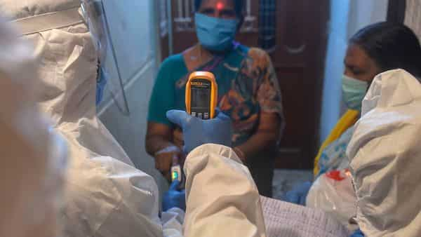Health workers check temperature of a woman during a free COVID-19 screening at a residential building (PTI)
