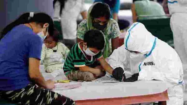 A medical worker helps a boy to draw inside a care centre for the coronavirus disease (COVID-19) patients at an indoor sports complex in New Delhi (REUTERS)