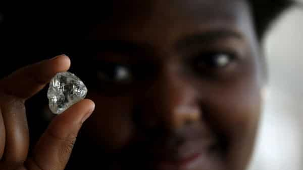 FILE PHOTO: A visitor holds a diamond during a visit to the De Beers Global Sightholder Sales (GSS) inGaborone, Botswana November 24, 2015. REUTERS/Siphiwe Sibeko/File Photo (REUTERS)