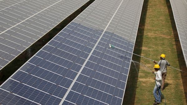 FILE PHOTO: Workers clean photovoltaic panels inside a solar power plant in Gujarat, India, (REUTERS)