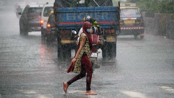 A woman crosses the street during the rain, in Mumbai on Sunday. (ANI Photo)