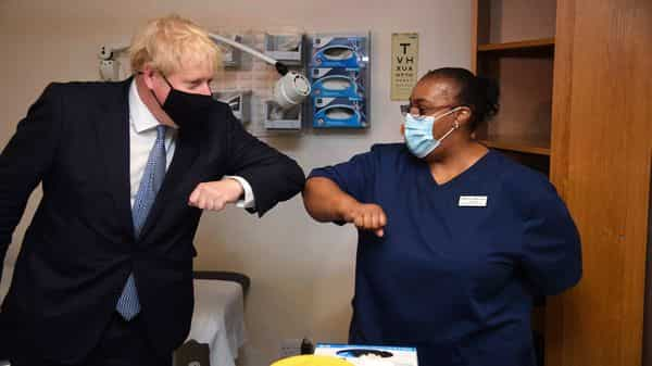Britain's Prime Minister Boris Johnson, left, elbow bumps Lead Nurse Marina Marquis, during a visit to Tollgate Medical Centre (AP)