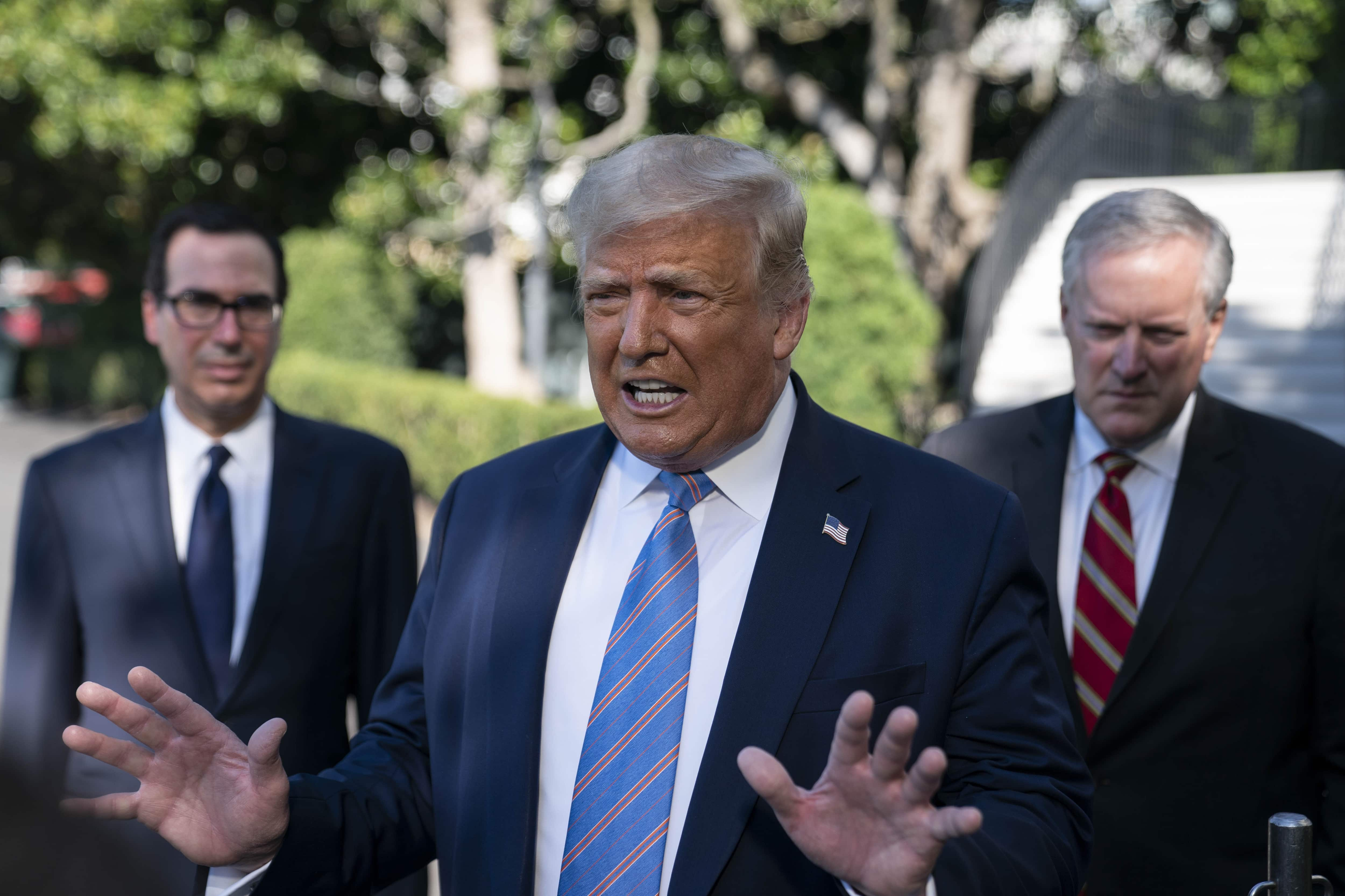 U.S. President Donald Trump speaks to members of the media as Steven Mnuchin, U.S. Treasury secretary, left, and Mark Meadows, White House chief of staff, right, listen before boarding Marine One on the South Lawn of the White House in Washington, D.C., U.S., on Wednesday, July 29, 2020. Trump will look to deep-pocketed energy barons to help jump start his sputtering re-election campaign today during a stop in Texas, a traditional Republican bastion that has become increasingly competitive for Democrats. Photographer: Sarah Silbiger/UPI/Bloomberg (Bloomberg)
