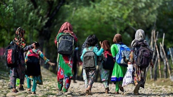 Schoolchildren walk towards their open-air school situated on top of a mountain in Doodhpathri, Kashmir